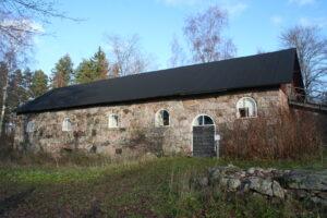 Harmaa kivinavetta, jossa musta katto, oviaukko ja neljä kaari-ikkunaa