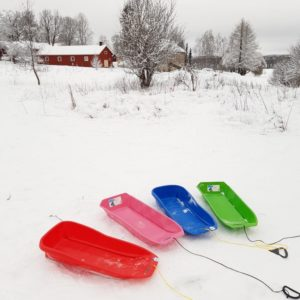 neljä pulkkaa lumell. Taustalla näkyy Lohjan museon ulkorakennuksia.