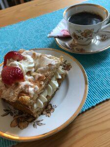 kopp kaffe och snygg torta på bord