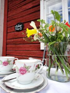 Kaksi kahvikuppia punaisen hirsirakennuksen edustalla ja kimppu keväisiä kukkia.